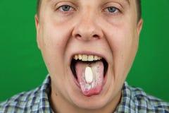 Jeune homme prenant une pilule photos stock