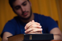 Jeune homme priant sur la Sainte Bible photographie stock