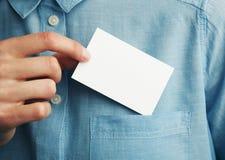 Jeune homme qui sort la carte de visite professionnelle vierge de visite de la poche de sa chemise photographie stock libre de droits