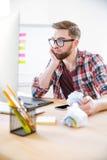 Jeune homme réfléchi avec la barbe fonctionnant et papier de froissement Photographie stock libre de droits