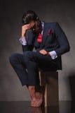 Jeune homme réfléchi d'affaires s'asseyant sur une boîte en bois photo stock