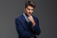 Jeune homme réfléchi de brune dans la veste bleue pensant à quelque chose Photographie stock libre de droits