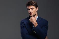 Jeune homme réfléchi de brune dans la veste bleue pensant à quelque chose Photos libres de droits