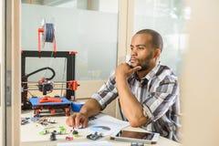 Jeune homme réfléchi machinant l'imprimante 3d Photos libres de droits
