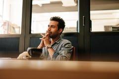 Jeune homme réfléchi s'asseyant à la table dans la salle de conférence Photographie stock libre de droits