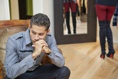 Jeune homme réfléchi s'asseyant avec l'amie à l'arrière-plan Photos stock