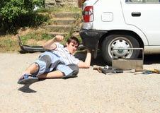 Jeune homme réparant la lumière cassée de voiture Photographie stock libre de droits