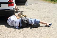Jeune homme réparant la lumière cassée de voiture Photo stock