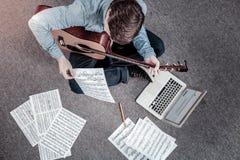 Jeune homme réussi apprenant la notation musicale images libres de droits