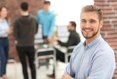 Jeune homme réussi d'affaires se tenant avec ses collègues à b photographie stock