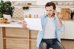 Jeune homme raidi parlant au téléphone photo stock