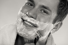 Jeune homme rasant utilisant le rasoir avec la mousse crème Photographie stock