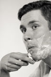 Jeune homme rasant utilisant le rasoir avec la mousse crème Image libre de droits