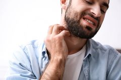 Jeune homme rayant le cou Sympt?mes d'allergies photographie stock libre de droits