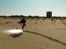 Jeune homme recherchant par le sable avec la lumière Images stock