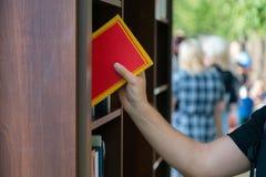 Jeune homme recherchant un livre dans la librairie Jeune étudiante féminine asiatique dans la robe d'obtention du diplôme, d'isol images libres de droits