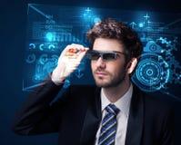 Jeune homme regardant avec les verres de pointe futés futuristes Images libres de droits
