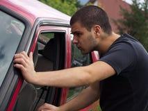 Jeune homme regardant dans le véhicule Photographie stock libre de droits