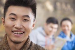 Jeune homme regardant l'appareil-photo, amis regardant la carte sur le fond, portrait Images stock