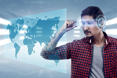 Jeune homme regardant la carte du monde avec des glas de pointe futés futuristes Photographie stock libre de droits