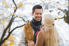Jeune homme regardant la femme en parc pendant l'automne Images stock