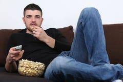Jeune homme regardant la TV et mangeant du maïs éclaté Image stock