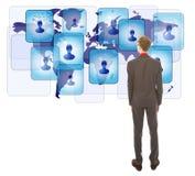 Jeune homme regardant ses amis virtuels d'isolement Image stock