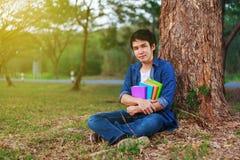 Jeune homme reposant et tenant un livre en parc Photographie stock