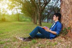 Jeune homme reposant et tenant un livre en parc Photo stock