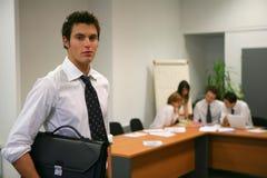Jeune homme restant au bureau photographie stock
