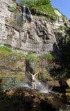 Jeune homme restant sous la cascade à écriture ligne par ligne avec l'arc-en-ciel Photographie stock
