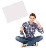 Jeune homme retenant l'affiche blanc Photographie stock