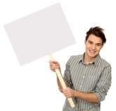 Jeune homme retenant l'affiche blanc Photos libres de droits