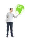 Jeune homme retenant la terre verte de planète Image stock