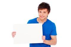 Jeune homme retenant le panneau-réclame blanc Photo libre de droits