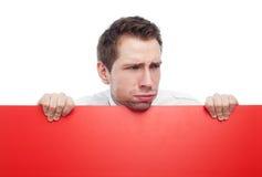 Jeune homme retenant le signe blanc rouge ricanant Photographie stock libre de droits