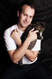 Jeune homme retenant un chat Photos stock
