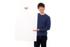 Jeune homme retenant un panneau blanc Photographie stock libre de droits