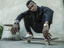 Jeune homme am?ricain d'africain noir attirant et s?rieux s'accroupissant sur le panneau de patin au coin de la rue grunge sembla image libre de droits