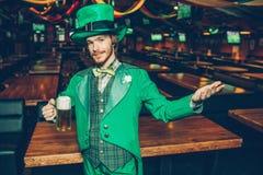 Jeune homme roux dans la tasse verte de participation de costume de la bière et du regard sur la caméra Il tiennent la main de cô image stock