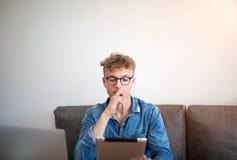 Jeune homme sérieux à l'aide du comprimé numérique et de l'ordinateur portable pour la plate-forme en ligne de service d'esthétiq image stock