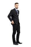 Jeune homme sérieux d'affaires mettant le téléphone portable dans sa vue de côté de poche de pantalon Photos libres de droits