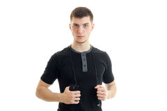 Jeune homme sérieux dans la chemise noire avec le smartphone dans des ses mains regardant l'appareil-photo Photos stock