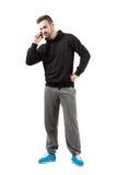 Jeune homme sérieux dans les vêtements de sport parlant au téléphone portable Photo libre de droits