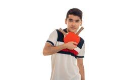 Jeune homme sérieux de brune jouant le ping-pong d'isolement sur le fond blanc dans le studio Photographie stock libre de droits