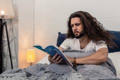 Jeune homme sérieux lisant un livre sur l'astrologie photos libres de droits