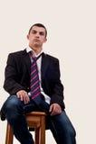 Jeune homme sérieux s'asseyant sur la chaise Photos stock