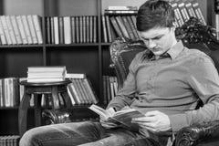 Jeune homme sérieux s'asseyant sur un livre de lecture de chaise Images stock