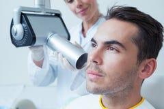 Jeune homme sérieux subissant le contrôle dentaire Image libre de droits
