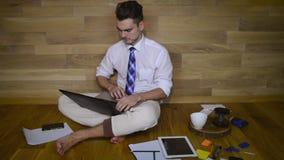 Jeune homme sérieux travaillant à la maison dans le pantalon drôle banque de vidéos